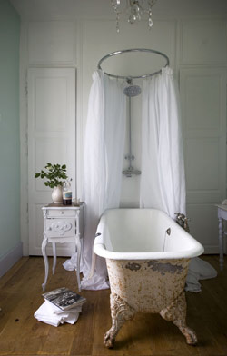An antique, cast-iron, clawfoot tub draped with curtain panels and a chandelier overhead is fit for a princess.