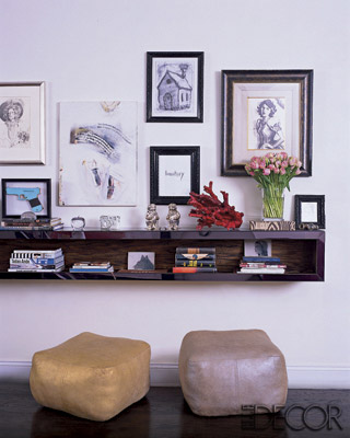 A living room landing strip displays books, artwork, and personal artifacts. A set of poufs serve as spare seating.