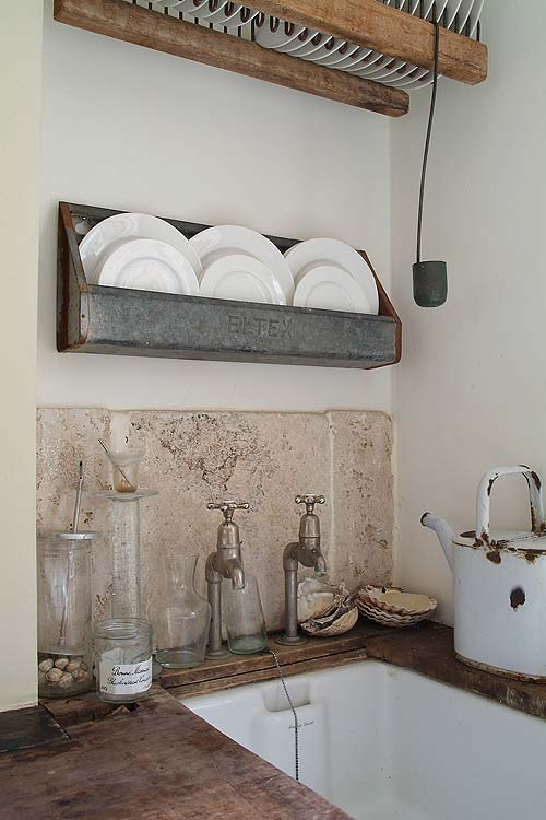 Old things — empty jam jars, found sea shells, a rusted watering can — are new again in this kitchen corner.