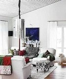 Colorful throws and cushions in the living room assimilate nicely against the white walls.