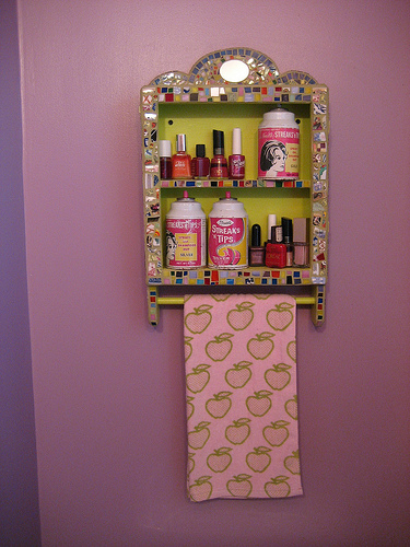 Laurel made the mosaic on this shelf, which is filled with vintage bath product jars.