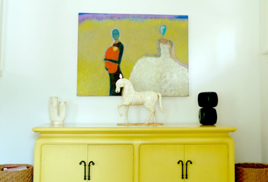 You can see already that sunny yellow is a theme throughout this residence. Here, the console color picks up the soft tones in the oil painting.