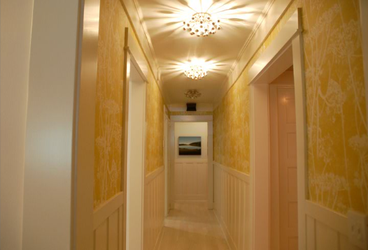 In this hallway, the bursting shadows of the ceiling lights mimic the botanical wallpaper print.