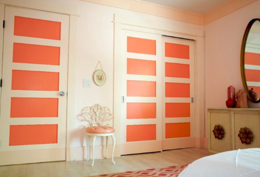 Rectangular door moldings painted in cheerful coral enliven an otherwise simple wall.