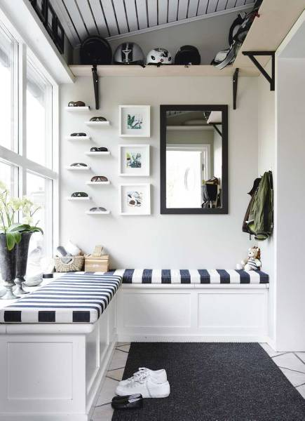 In this hallway, space near the ceiling makes clever storage, and even the seating has built-in storage. A collection of sunglasses is displayed on simple shelves.