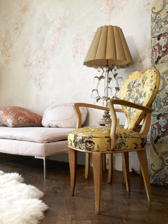 The heart-shaped chair with Danish-style legs, upholstered in yellow toile, adds an unexpected touch to the shabby chic French sitting area.