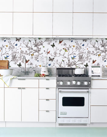 Or, put away that paint brush and roll out a sheet of wallpaper. The cheerful, busy wallpaper adds an element of surprise to this otherwise white kitchen. Choose one with hints of the color in nearby rooms to pull it all together. Source
