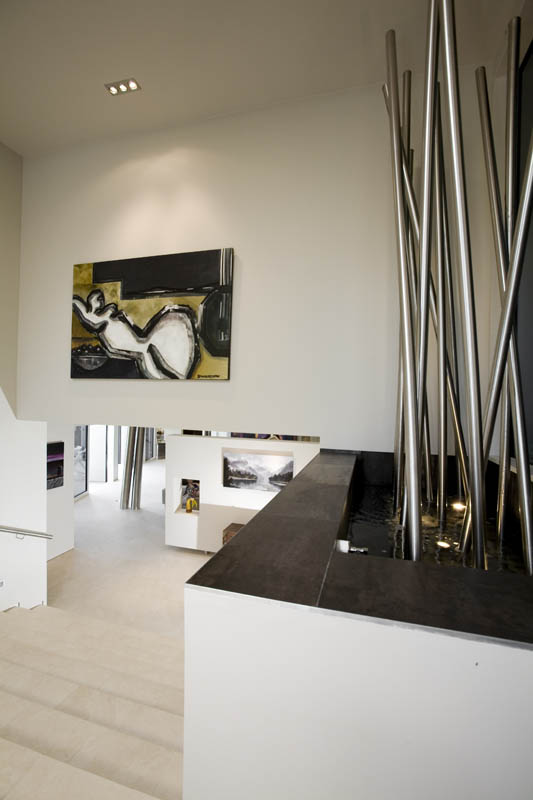 Stainless steel pillars rise out of a fountain inside the home's entrance. The water sculpture was custom designed, and it separates the living area from the entry.