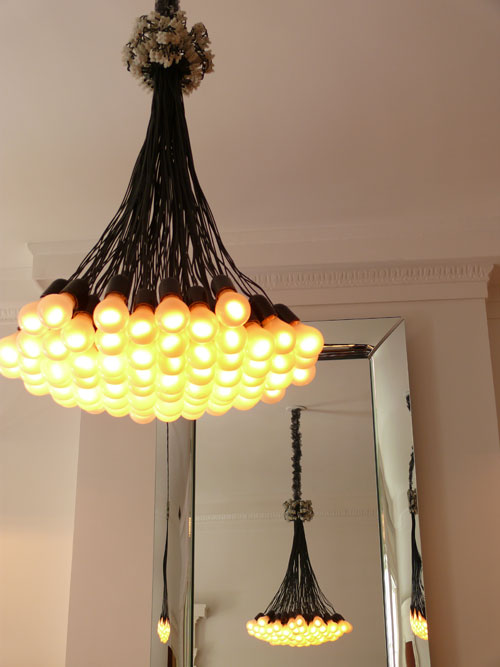 The Droog 85 Lamp Chandelier ($3,462) makes a statement reflecting in the Starck mirror.