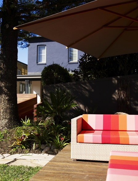 Weather-resistant outdoor furniture and a wide shade structure combine to make a perfect outdoor seating arrangement.