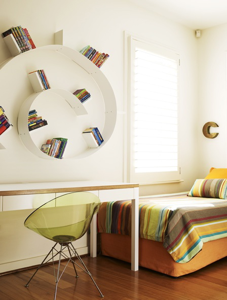 A circular book shelf blends into the white wall, so the books almost appear to float.
