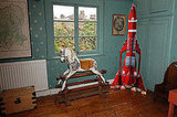 An antique rocking horse cozies up next to a rocket model. Quite the change in modes of transportation!