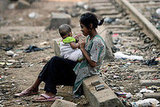 A girl sits near the tracks with her younger sibling near the home of child actor Rubina Ali.
