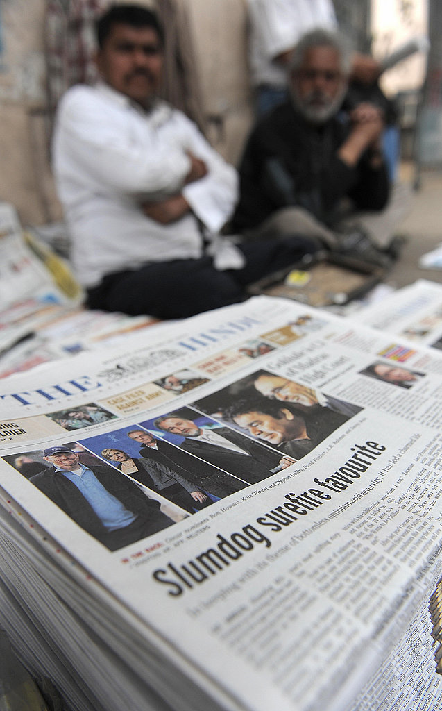 A newspaper vendor waits by a paper announcing the news.