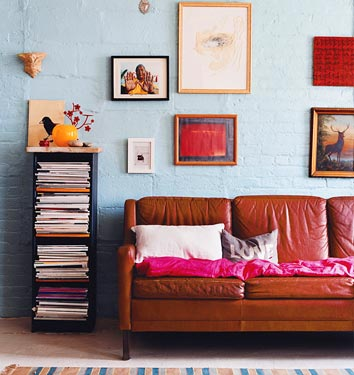 A hot pink throw can liven up even an old and faded leather sofa in Lili Diallo's apartment, proving that anything can be worked with, if you love it enough. Source