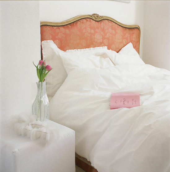 Ultra-feminine and serene, comfy and loose white bedding with delicate pleated trim and a gorgeous headboard are graceful and girlish. Source