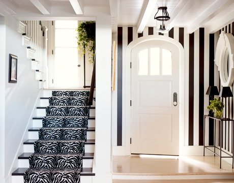 This entryway was painted with black-and-white striped walls, channeling Dorothy Draper, and giving the house a bold first impression. Source